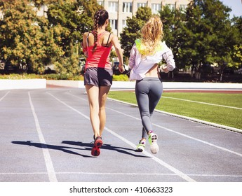 Runners on the stadium track. Women summer fitness workout. Jogging, sport, healthy active lifestyle and friendship concept