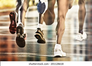 Runners on wet ground with city reflection