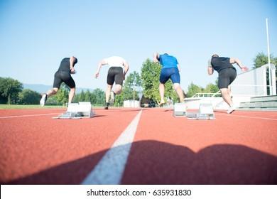 Runners preparing for race at starting blocks