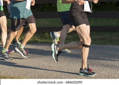 Runners running a 5000 meter rave on a sunny night in the summer