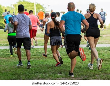 Runners running on grass away from the camera during a 10K summer series race at Sunken Meadow State Park.