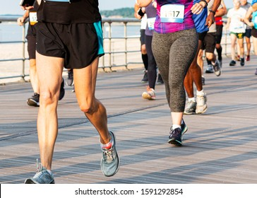 Runners in shorts and spandex on a boardwalk running a 10K at Sunken Meadow State Park over the summer.