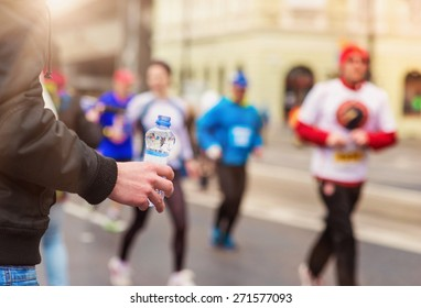 Runners taking a water bottle at the refreshment point in the city competition