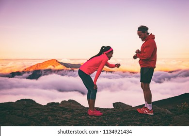 Runners tired exhausted during cardio effort using their wearable technology smartwatch checking heart rate monitor. Two athletes couple running together in outdoors mountains landscape.