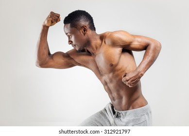 Running african american man over the light background with persistent look