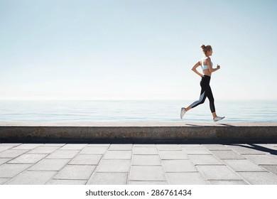 Running asian woman. Female runner training outdoors seaside athlete on beautiful sunset or morning at beach.