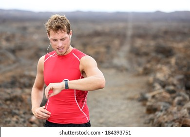 Running athlete man looking at smartwatch heart rate monitor GPS smart watch. Runner listening to music in earphones. Athlete resting tired after training on Big Island, Hawaii, USA.