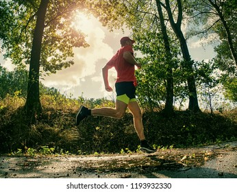 Running athlete man. Male runner sprinting during outdoors training for marathon run. Athletic fit young sport fitness model, fall wet road outside in nature.