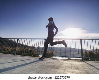 Running athlete man, side full body view. Male runner sprinting during outdoors training. Regular morning runner