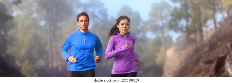 Running athletes jogging on trail run - active healthy lifestye panorama banner. Couple runners interracial Asian woman, Caucasian man training cardio in forest.