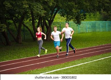 Running athletes at stadium.