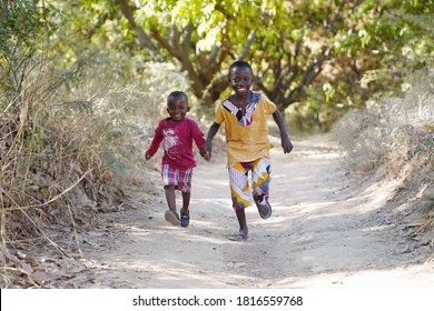 Running Black African Ethnicity Boys Having Fun Smiling and Laughing in Typical African Village Town