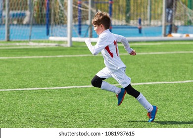 Running boy soccer player training on the football field