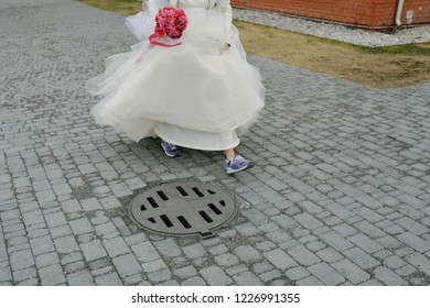 Running bride. ( Runaway bride ). A girl in a wedding dress and sneakers running down the street. Runs to his happiness
