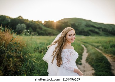 Running bride. Wedding couple at sunset. The bride in a white dress. beautiful nature, path to the forest, green grass. Wedding photo session at sunset.