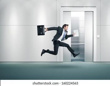 Running businessman and open lift door