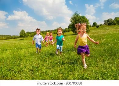 Running children in green field during summer