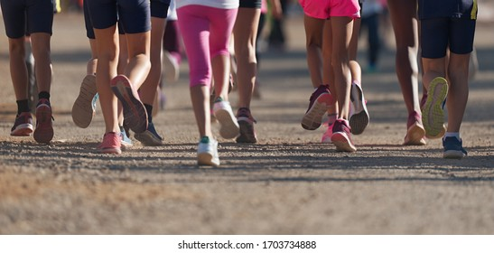 Running children, young athletes running in a kids run race, running on a park road detail on legs, running in the light of morning