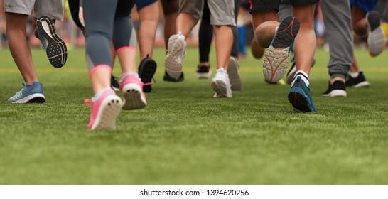 Running children, young athletes run in a kids run race, running on grass detail on legs, running in the light of morning