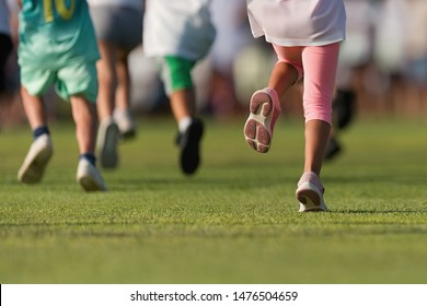 Running children, young athletes run in a kids run race, running on grass detail on legs, running in the light of morning