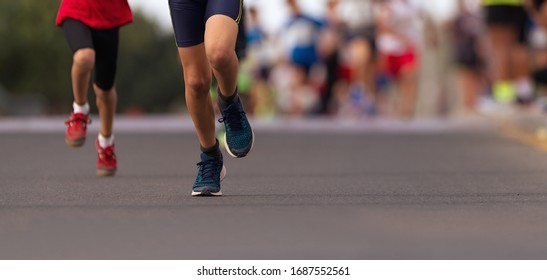 Running children, young athletes run in a kids run race, running on city road detail on legs