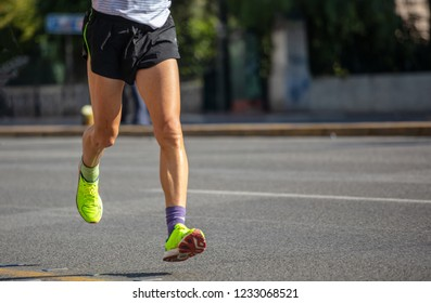 Running in the city roads. Young man runner, front view, blur background, copy space, detail on legs