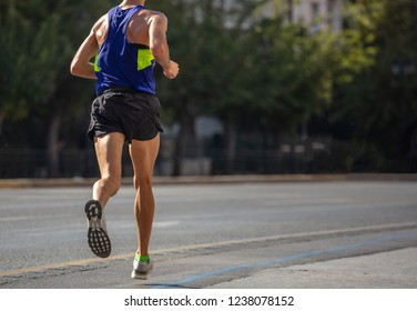 Running in the city roads. Young man runner, back view, blur background, copy space