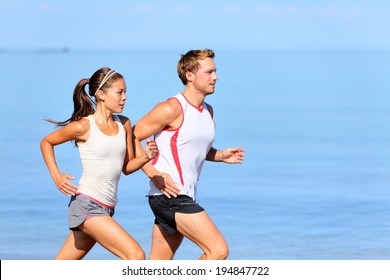 Running couple jogging on beach. Runners training together. Man and woman joggers exercising outdoors.