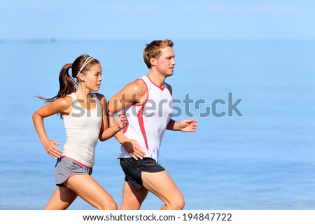 running couple jogging on beach 450w 194847722