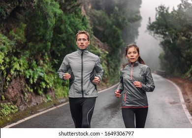 Running couple on wet park trail jogging in rain wearing sportswear jackets in cold weather. Asian woman, Caucasian man athletes training cardio.