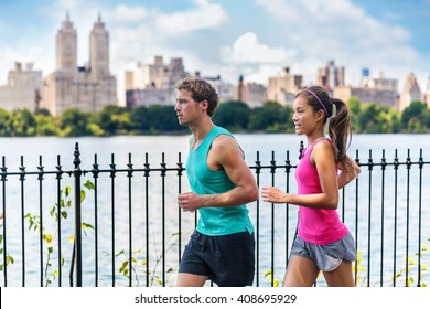 Running couple runners jogging in Central Park, NYC living healthy fitness lifestyle. People running summer training for marathon in Manhattan, New York. Asian female model and Caucasian male athlete.