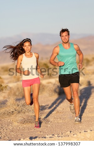 5e69be8f Running couple - runners jogging on trail run path outside in beautiful  nature. Asian woman runner and Caucasian male fitness sport model jogger  training ...