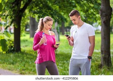 Running couple using mobile phone after jogging in park