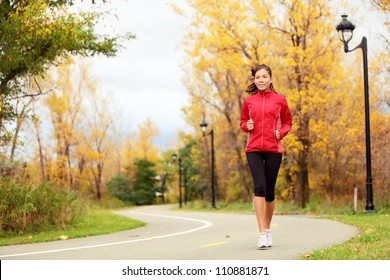 Running in Fall. Runner woman jogging in autumn forest. Beautiful young fit fitness sport model jogging with slight motion blur. Mixed race Caucasian / Asian girl.
