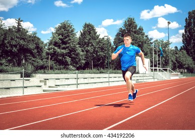Running fast on athletic track. Young adult man sprinting fast during hot summer day. Toned image.