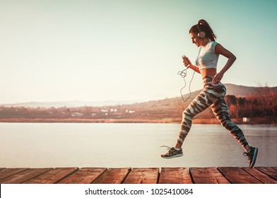 Running fit woman with headphones outdoors