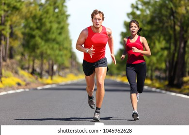 Running fitness couple of runners doing sport on road outdoor. Active living man and woman jogging training cardio in summer outdoors nature. Asian girl, caucasian athletes.