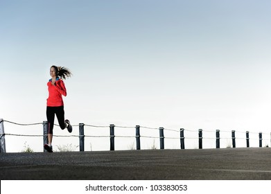 Running fitness training woman outdoors. Action healthy lifestyle image with copyspace