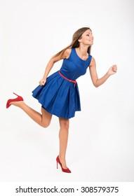 Running girl in blue dress, studio full length portrait