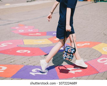 Running girl. Jumping girl. Woman is playing hopscotch. Summer time, warm and sunny weather. Lifestyle, urban and casual style. Sports girl. Figures painted on asphalt.
