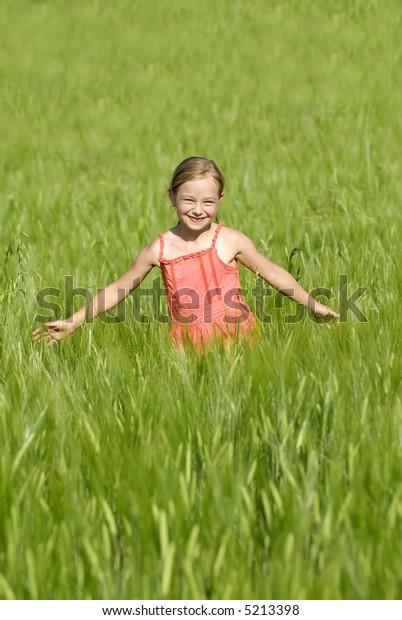Running girl on green field
