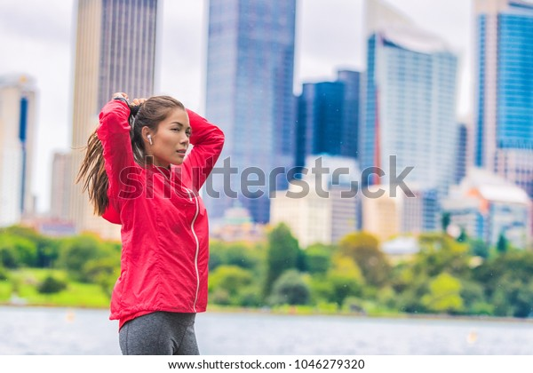 Running healthy lifestyle in urban runner Asian woman getting ready to run morning cardio exercise.