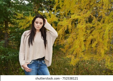Running her fingers through her hair, the young woman with long dark hair looks downward while standing in the tamarck / larch tree with yellow needles