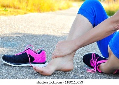 Running injury leg accident- sport woman runner hurting holding painful sprained ankle in pain.Athlete woman has ankle injury, sprained ankle during running training.Space for text