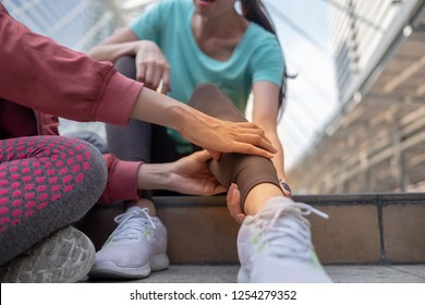 Running injury leg accident- sport woman runner hurting holding painful sprained ankle in pain, someone help to first aid before move to hospital.