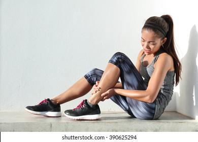 Running injury leg accident- sport woman runner hurting holding painful sprained ankle in pain. Female athlete with joint or muscle soreness and problem feeling ache in her lower body.