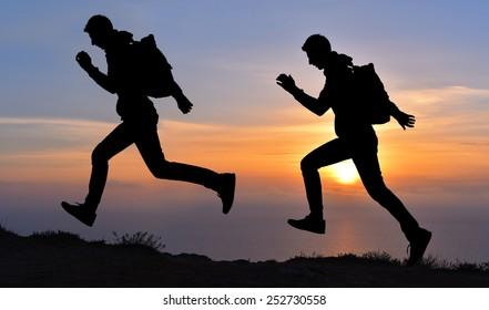Running jumping man above sunset and mountain. Sport sky sun nature