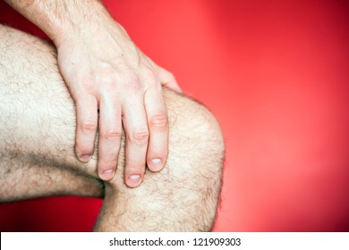 Running knee injury, runner leg pain, sore and exercising. Man holding sore knee, hand massage over red background. Fitness exercise concept.