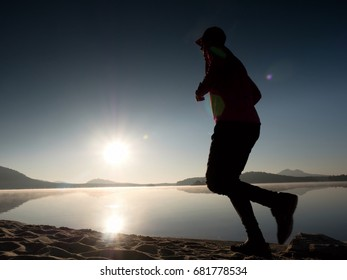 Running man. Boy quickly running on the morning beach. Sportsman runner, jogging guy during the sunrise above sandy beach