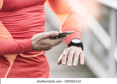 Running man checking sport performance on his mobile phone and smart-watch app